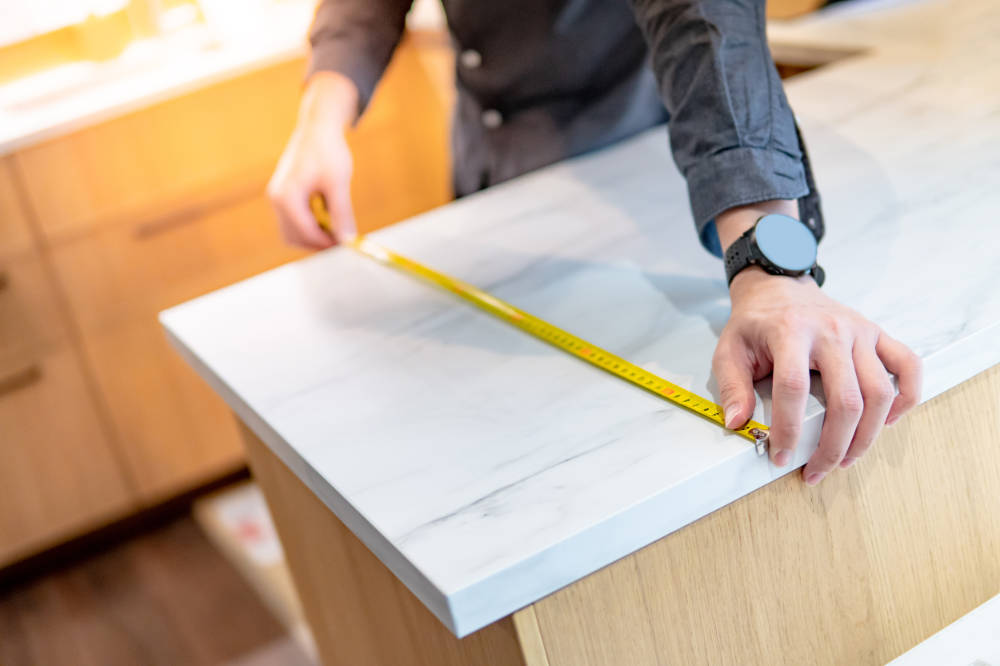 A guy using a measure tape across a peninsula kitchen countertop taking measurements